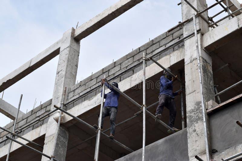 Filippinska byggnadsarbetare som installerar metall, leda i rör ställningar på höghus utan den skyddande dräkten royaltyfri foto