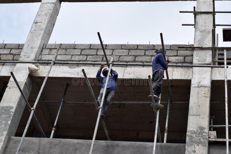 Filippinska byggnadsarbetare som installerar metall, leda i rör ställningar på höghus utan den skyddande dräkten royaltyfria foton