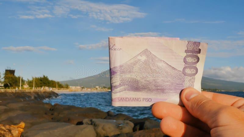 Filippinska pengar En filippinsk monetär anmärkning i hundra pesos är hängiven till den Mayon vulkan royaltyfri bild