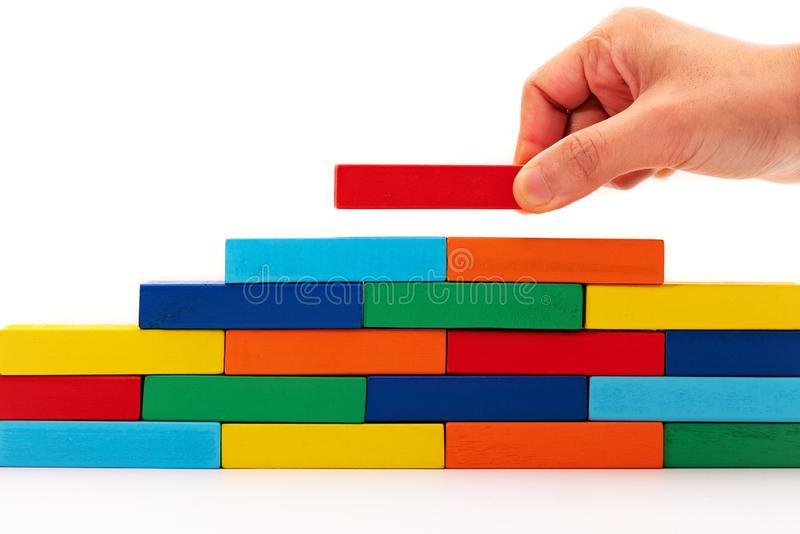 Fill in business solutions concept, a piece of wooden block puzzle put on top of wooden stack royalty free stock photo