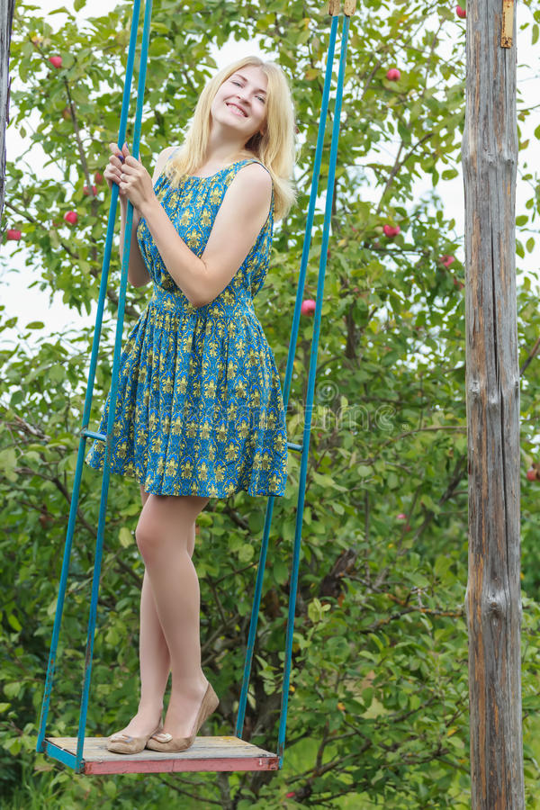 Fill length portrait of blonde girl in silk sundress on handmade swing. Fill length portrait of blonde girl in blue silk sundress on handmade swing stock photos