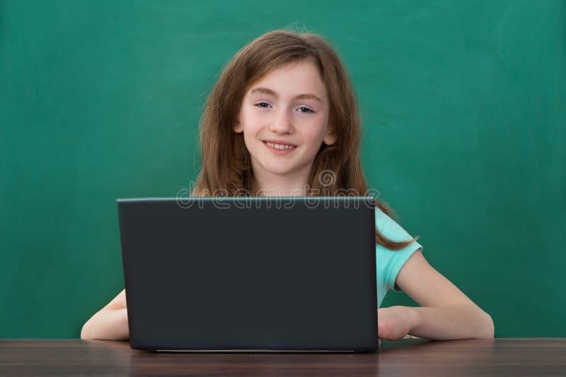 Fille à l'aide de l'ordinateur portable dans la salle de classe images libres de droits