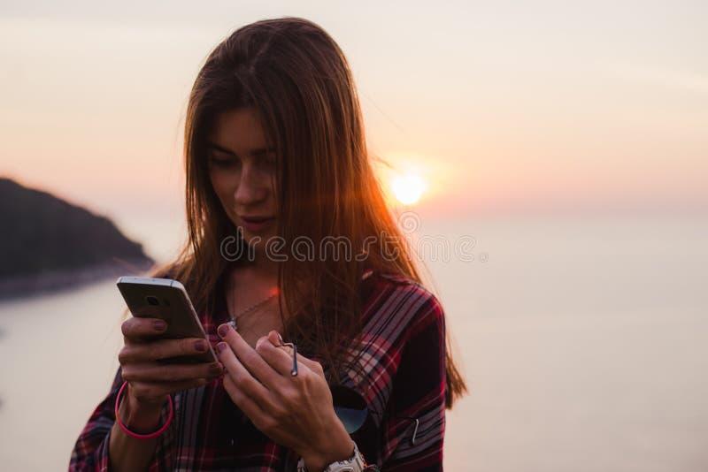 Fille à l'aide du téléphone portable près de la mer dans le lever de soleil ou le coucher du soleil images libres de droits