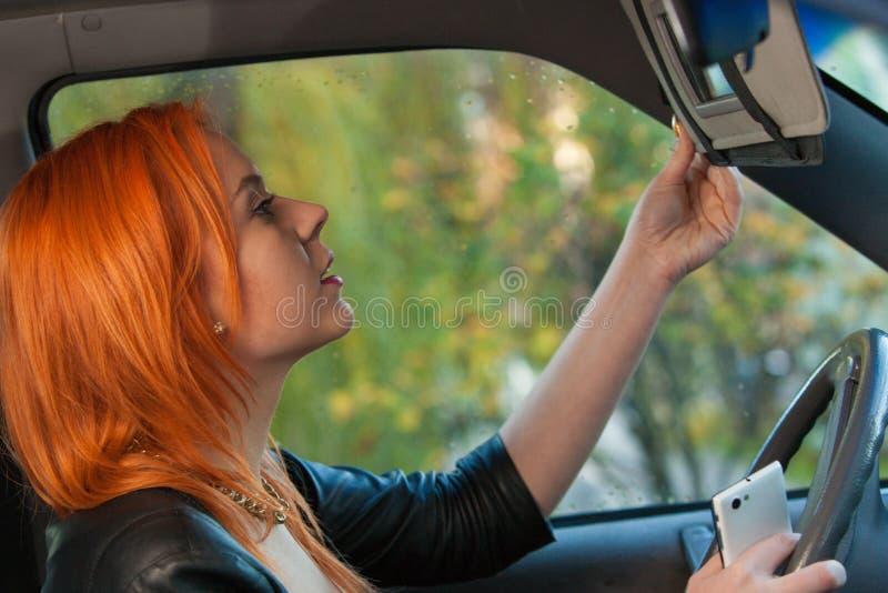 Fille à l'aide du téléphone regardant le miroir tout en conduisant la voiture photo libre de droits