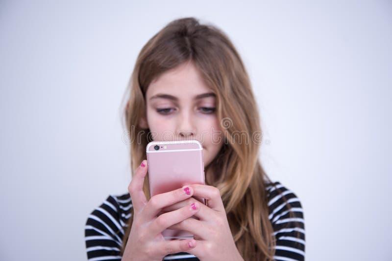 Fille à l'aide du téléphone rose dans le moment de serius image libre de droits