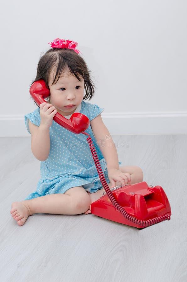 Fille à l'aide du téléphone sur le plancher photos libres de droits