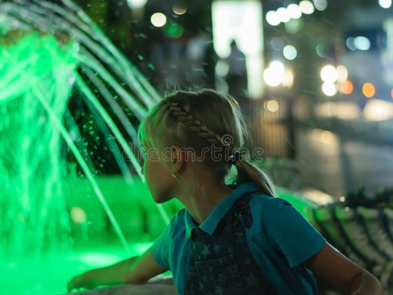 Fille à la fontaine dans la ville la nuit dans la lampe au néon photo stock