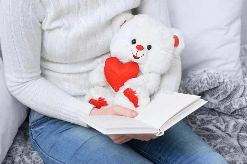 Fille à la maison lisant un livre et tenant un jouet d'ours blanc photo stock