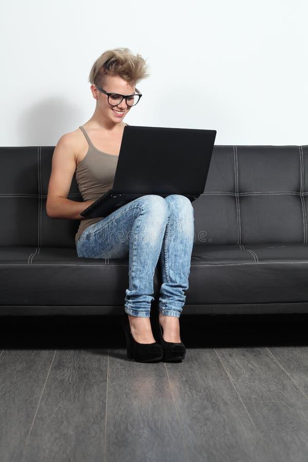 Fille à la mode d'adolescent s'asseyant sur un divan avec un ordinateur portable et des verres photo libre de droits