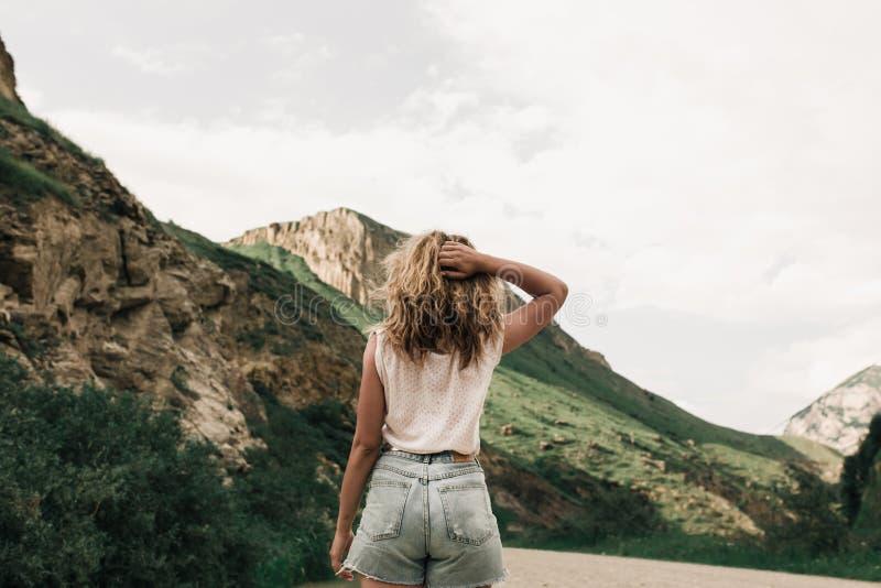 Fille à la mode dans des vêtements blancs se tenant sur la route dans les montagnes Herbe verte et montagnes photo libre de droits