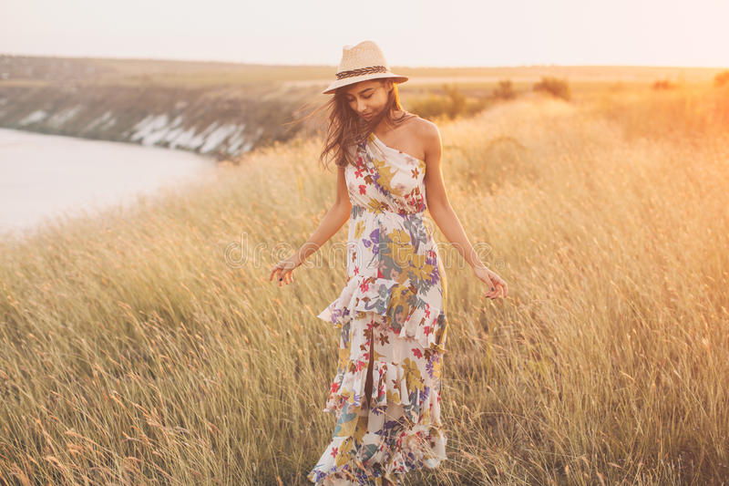 Fille à la mode dans la robe élégante d'été avec le beau chapeau photographie stock