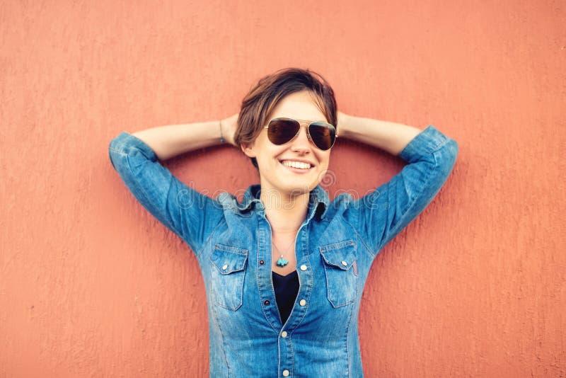 Fille à la mode de brune, faisant des expressions de visage, souriant et riant sur le fond orange, d'isolement Style de vie moder image stock