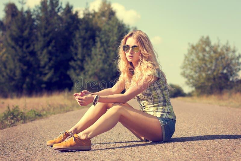 Fille à la mode de hippie s'asseyant sur la route image stock