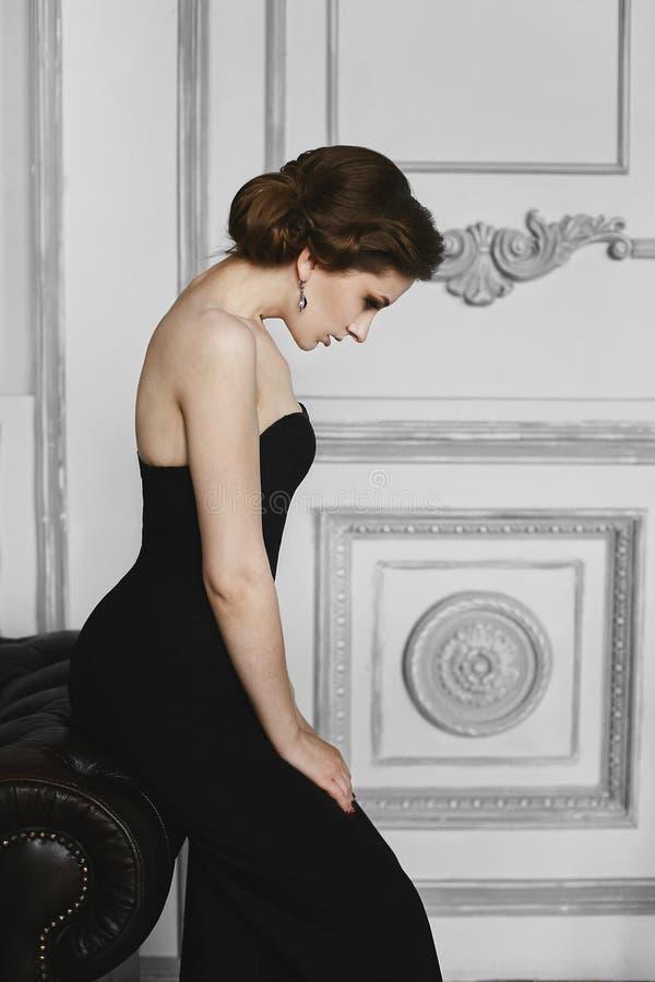 Fille à la mode et belle de modèle de brune dans la robe noire posant au fond de luxe, à l'intérieur image stock