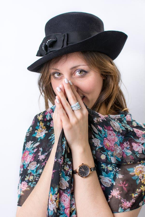 Fille à la mode posant utilisant un chapeau noir images stock