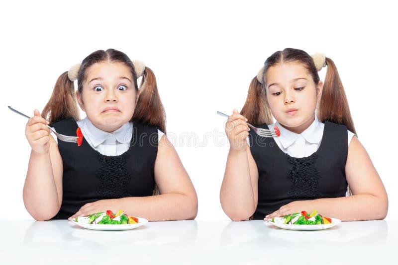 Fille à la table mangeant de la salade, enfant de poids excessif nutrition appropriée pour des écoliers photos libres de droits