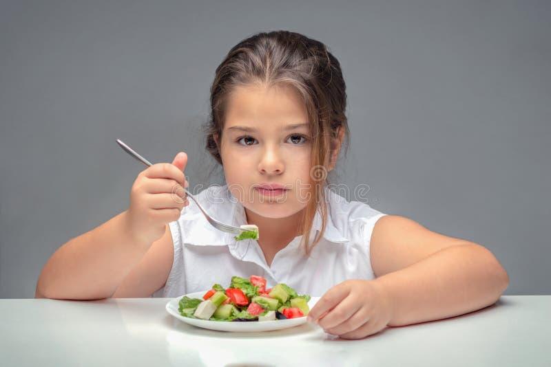 Fille à la table mangeant de la salade, enfant de poids excessif image stock
