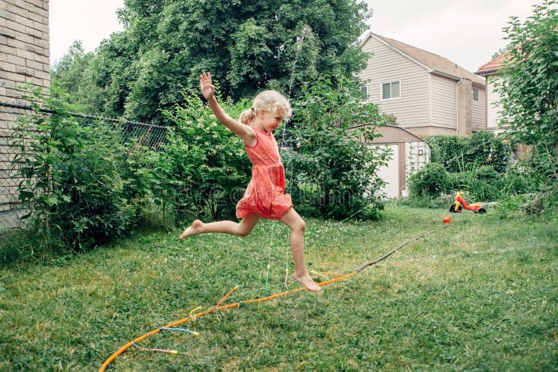Fille éclaboussant de l'arroseuse de tuyau de jardinage sur l'arrière-cour le jour d'été photos stock