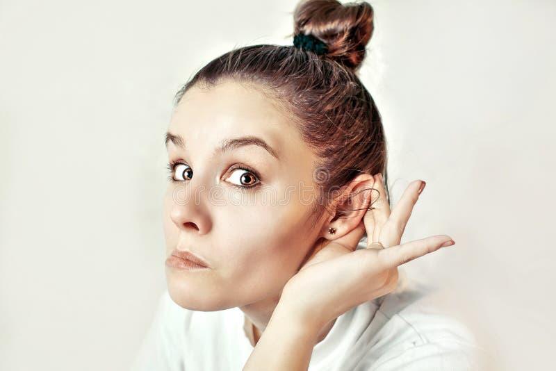 Fille écoutant avec sa main sur une oreille photo stock