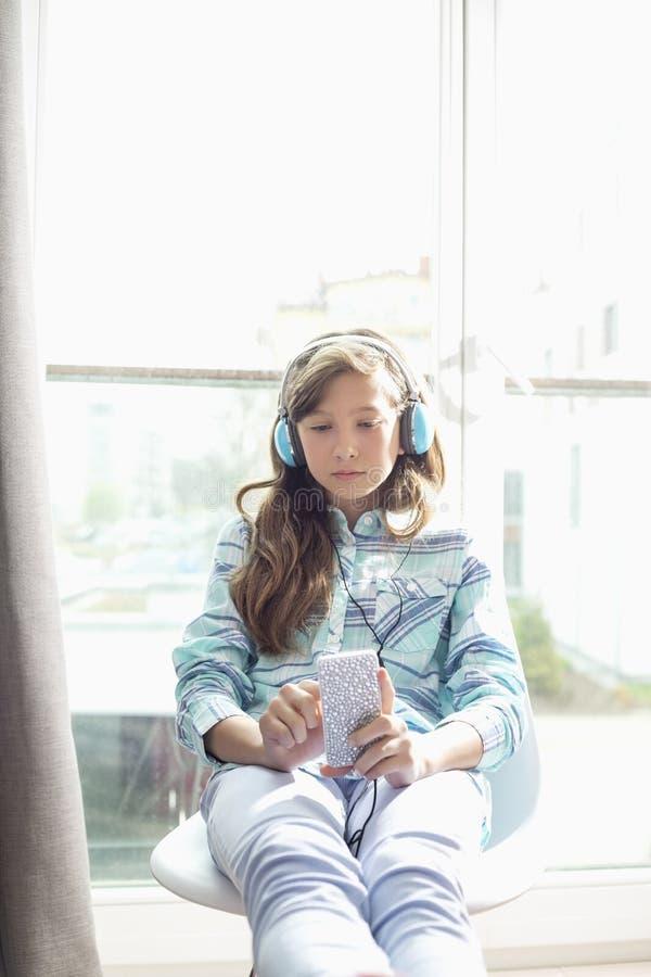 Fille écoutant la musique à la maison photo libre de droits