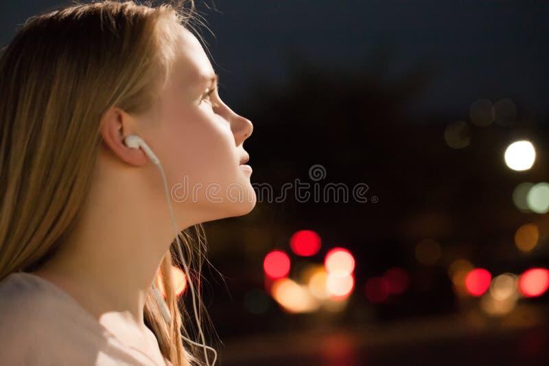 Fille écoutant la musique avec des écouteurs sur le fond de ville de nuit photographie stock