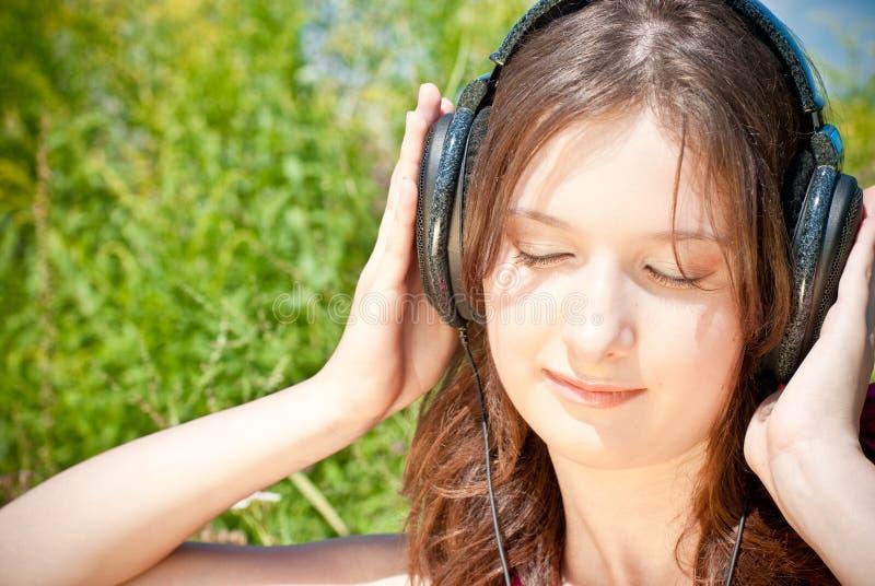 Fille écoutant la musique dans des écouteurs image libre de droits