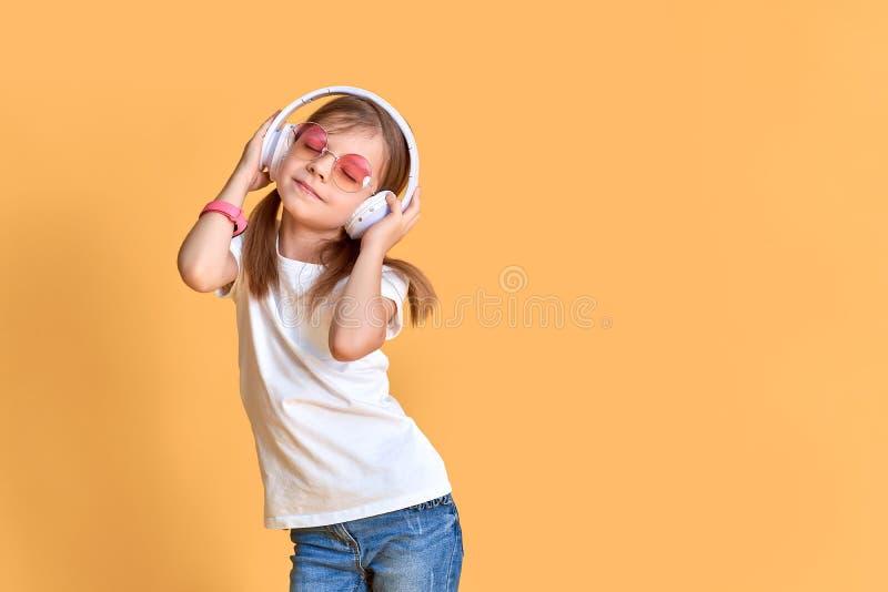 Fille écoutant la musique dans des écouteurs sur le fond jaune Enfant mignon appr?ciant la musique de danse heureuse, l'oeil ?tro photo libre de droits