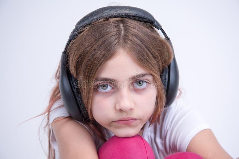 Fille écoutant la musique triste sur l'écouteur image libre de droits