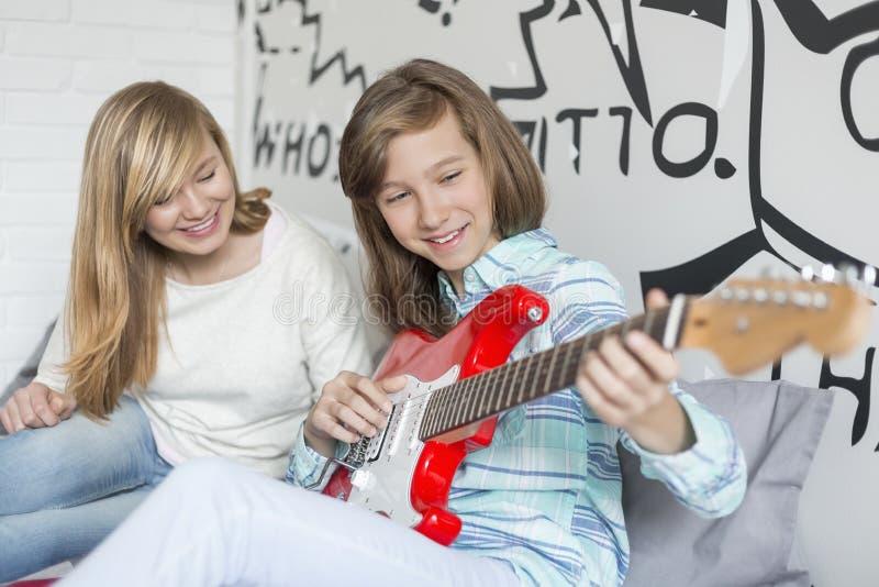 Fille écoutant la soeur jouant la guitare à la maison image stock