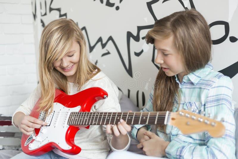 Fille écoutant la soeur jouant la guitare électrique à la maison photographie stock libre de droits