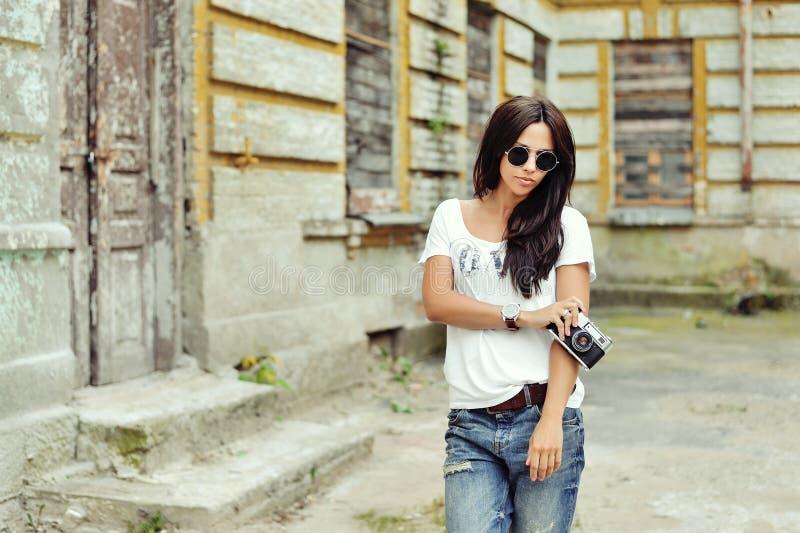 Fille élégante à la mode avec les lunettes de soleil de port de vieil appareil-photo et photos stock