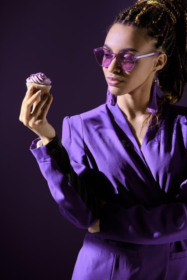Fille élégante d'afro-américain dans la veste ultra-violette et des lunettes de soleil regardant le petit gâteau, photographie stock