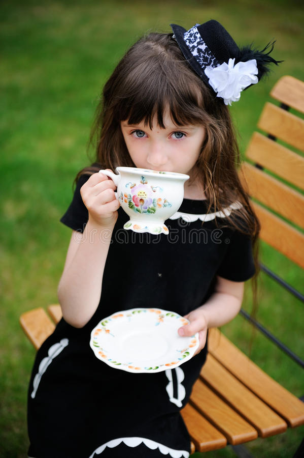 Fille élégante d'enfant ayant une réception de thé à l'extérieur photographie stock libre de droits