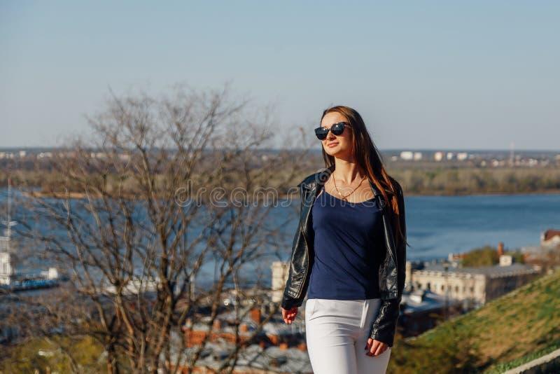Fille élégante dans des lunettes de soleil avec de longs cheveux et une veste en cuir photographie stock