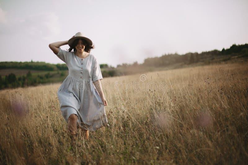 Fille élégante dans la robe de toile fonctionnant parmi des herbes et des wildflowers dans le pré ensoleillé en montagnes Femme d photos libres de droits