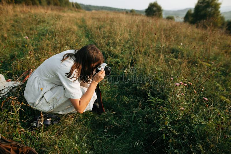 Fille élégante de boho prenant la photo sur la caméra analogue de photo de film de l'herbe et des wildflowers dans le pré ensolei photo libre de droits