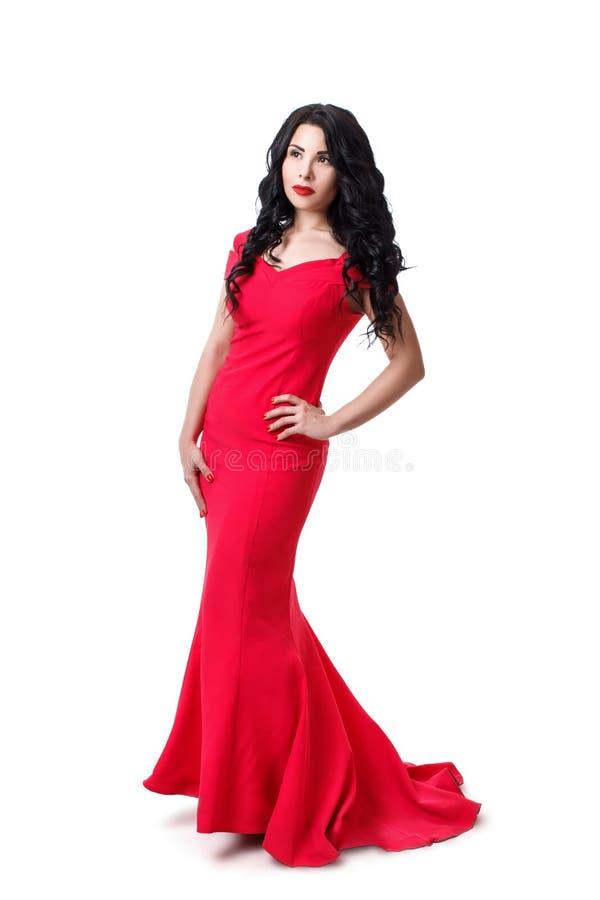 Fille élégante de brune dans des cheveux bouclés noirs dans une robe de soirée rouge D'isolement sur le fond blanc image libre de droits