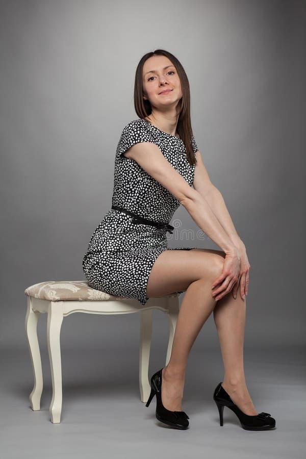 Fille élégante de brune dans la robe se reposant sur une chaise photo libre de droits
