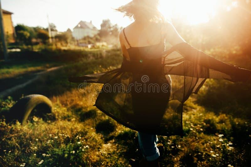 Fille élégante de hippie ayant l'amusement dans le parc ensoleillé dans les rayons de soleil stupéfiants, moment atmosphérique Da photos stock