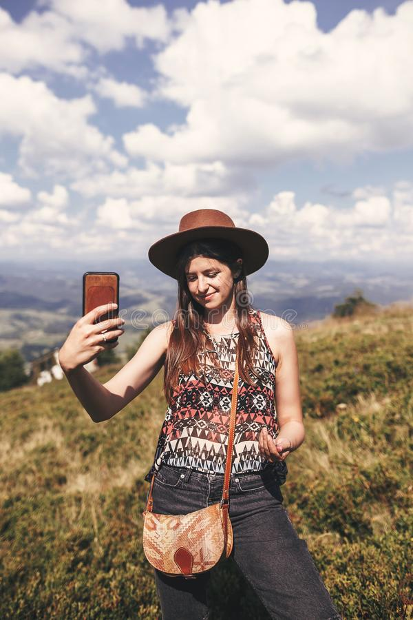 Fille élégante de hippie en téléphone de participation de chapeau et photo de fabrication sur les montagnes ensoleillées Jeune fe images stock