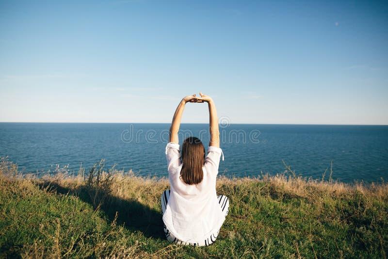 Fille élégante de hippie reposant et faisant le yoga sur la crête de montagne avec la vue sur la mer et le ciel Yoga de pratique  images stock