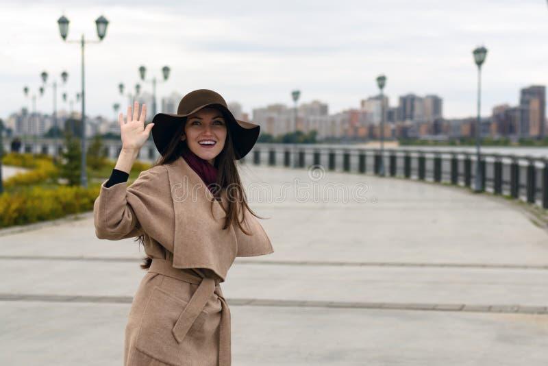 Fille élégante heureuse dans un manteau avec la ceinture et la grande salutation de chapeau montrant le geste de main Le concept  image libre de droits