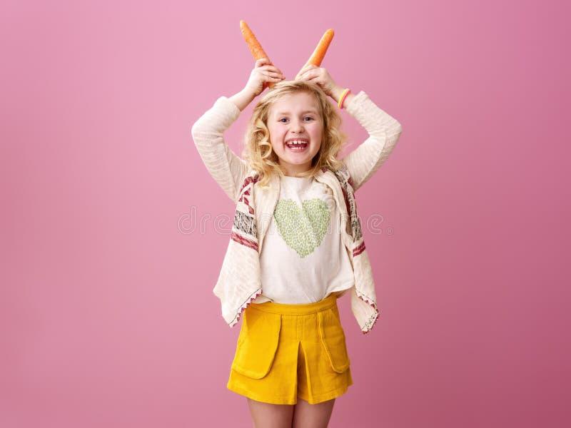 Fille élégante heureuse sur le fond rose faisant des klaxons à partir des carottes images libres de droits
