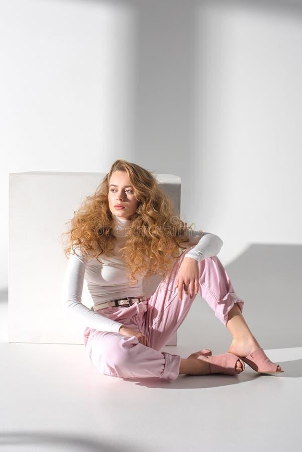 fille élégante sûre s'asseyant sur un plancher près du cube blanc et du regard photos stock