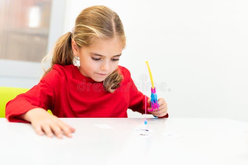 Fille élémentaire d'âge en session d'ergothérapie d'enfant faisant des exercices espiègles image libre de droits