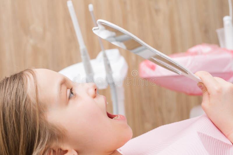 Fille élémentaire d'âge regardant ses dents dans le miroir dans la clinique dentaire pédiatrique image libre de droits