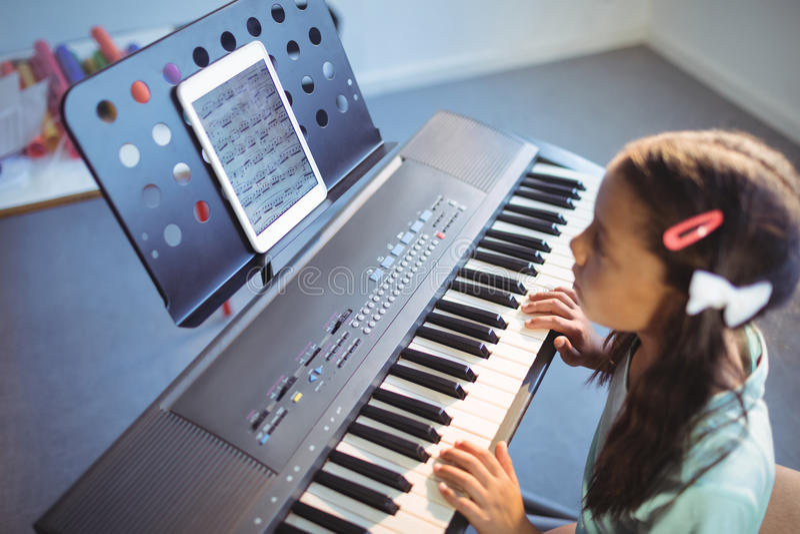Fille élémentaire regardant le comprimé numérique sur le support tout en pratiquant le piano photos stock
