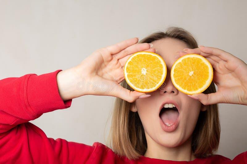 Fille émotive de brune posant avec une demi orange, couvrant des yeux, contre le mur blanc L'espace pour le texte image libre de droits