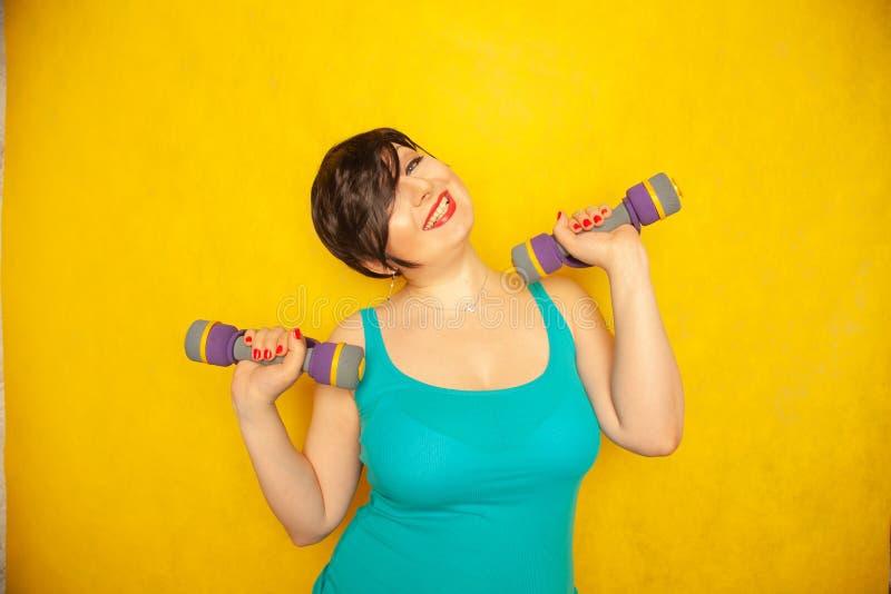 Fille émotive joyeuse potelée avec les cheveux courts dans un T-shirt bleu faisant des sports avec des haltères pour être sain et image stock