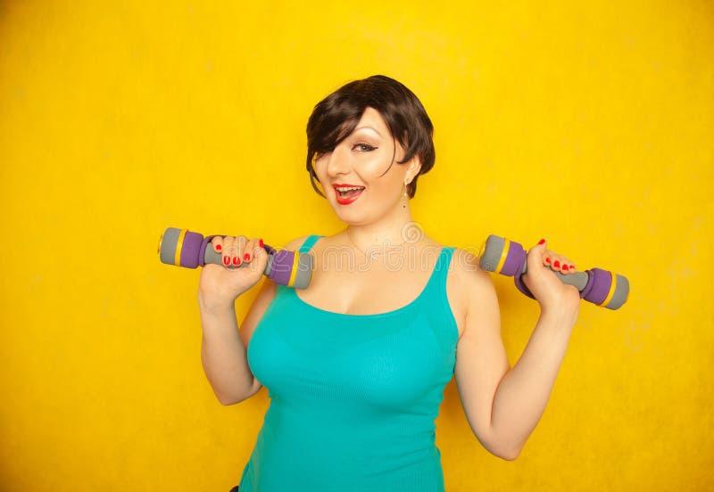 Fille émotive joyeuse potelée avec les cheveux courts dans un T-shirt bleu faisant des sports avec des haltères pour être sain et photo libre de droits